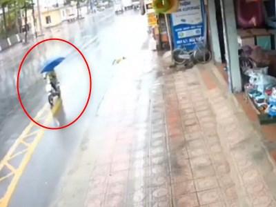 【衝撃映像】傘をさしながら電動スクーターに乗っていた人がこれからどうなるかをご覧ください